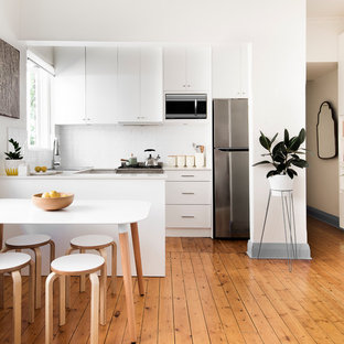 Small trendy u-shaped medium tone wood floor eat-in kitchen photo in Sydney with flat-panel cabinets, white cabinets, quartzite countertops, white backsplash, subway tile backsplash, stainless steel appliances and a peninsula