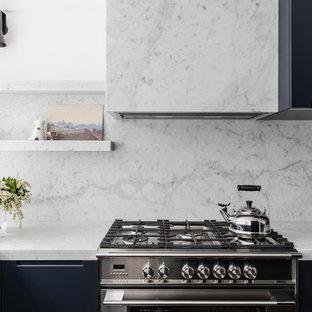 Ispirazione per una cucina minimalista di medie dimensioni con lavello sottopiano, ante lisce, ante blu, top in marmo, paraspruzzi in marmo, elettrodomestici in acciaio inossidabile, parquet scuro, nessuna isola e top blu