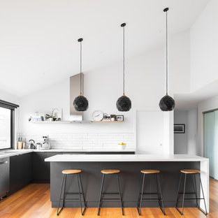 This is an example of a contemporary l-shaped kitchen in Hobart with an undermount sink, flat-panel cabinets, grey cabinets, white splashback, subway tile splashback, stainless steel appliances, medium hardwood floors, with island, brown floor and white benchtop.
