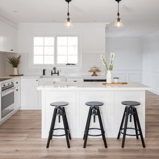 Inspiration for a mid-sized transitional l-shaped open plan kitchen in Sydney with a farmhouse sink, shaker cabinets, white cabinets, marble benchtops, white splashback, marble splashback, stainless steel appliances, laminate floors, with island, brown floor and white benchtop.