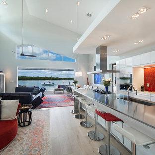 Diseño de cocina de galera, contemporánea, grande, abierta, con suelo de madera clara, armarios con paneles lisos, puertas de armario blancas, salpicadero rojo, electrodomésticos negros, una isla, encimera de acero inoxidable, fregadero integrado y salpicadero de azulejos de vidrio