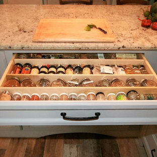 Inspiration för mellanstora lantliga kök, med en rustik diskho, luckor med upphöjd panel, grå skåp, granitbänkskiva, vitt stänkskydd, stänkskydd i tunnelbanekakel, rostfria vitvaror, klinkergolv i porslin och en halv köksö