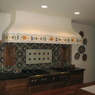フェニックスの大きいサンタフェスタイルのおしゃれなキッチン (エプロンフロントシンク、落し込みパネル扉のキャビネット、ヴィンテージ仕上げキャビネット、木材カウンター、マルチカラーのキッチンパネル、テラコッタタイルのキッチンパネル、パネルと同色の調理設備、塗装フローリング) の写真
