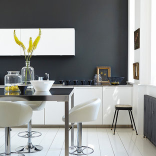 Contemporary kitchen in Belfast with flat-panel cabinets, white cabinets, black splashback, an island and white floors.