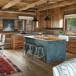 Aménagement d'une cuisine ouverte montagne en L avec un évier de ferme, un placard à porte shaker, des portes de placard en bois brun, un plan de travail en bois, une crédence marron, une crédence en bois, un électroménager encastrable, un sol en bois clair, un îlot central, un sol beige et un plan de travail turquoise.