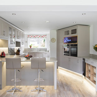 Medium sized traditional u-shaped enclosed kitchen in Other with a submerged sink, recessed-panel cabinets, grey cabinets, granite worktops, grey splashback, a breakfast bar, black appliances, light hardwood flooring and beige floors.