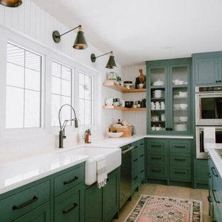 Große Stilmix Wohnküche in L-Form mit Landhausspüle, Schrankfronten mit vertiefter Füllung, grünen Schränken, Quarzwerkstein-Arbeitsplatte, Küchenrückwand in Weiß, Küchengeräten aus Edelstahl, hellem Holzboden, Kücheninsel, braunem Boden und weißer Arbeitsplatte in Kolumbus
