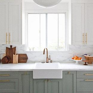 コロンバスの中くらいのコンテンポラリースタイルのおしゃれなキッチン (エプロンフロントシンク、落し込みパネル扉のキャビネット、緑のキャビネット、クオーツストーンカウンター、白いキッチンパネル、石スラブのキッチンパネル、シルバーの調理設備、濃色無垢フローリング、茶色い床、白いキッチンカウンター) の写真