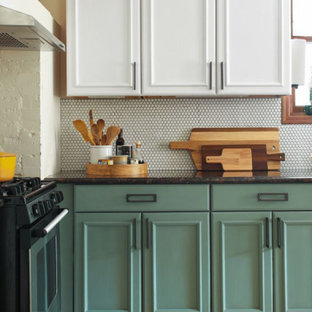 Small bohemian l-shaped kitchen pantry in Columbus with a belfast sink, recessed-panel cabinets, green cabinets, granite worktops, white splashback, ceramic splashback, stainless steel appliances, ceramic flooring, multi-coloured floors and black worktops.