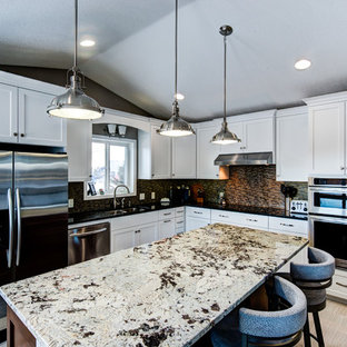 Example of a mid-sized transitional l-shaped porcelain floor and beige floor kitchen design in Minneapolis with a double-bowl sink, shaker cabinets, white cabinets, granite countertops, brown backsplash, matchstick tile backsplash, stainless steel appliances and an island