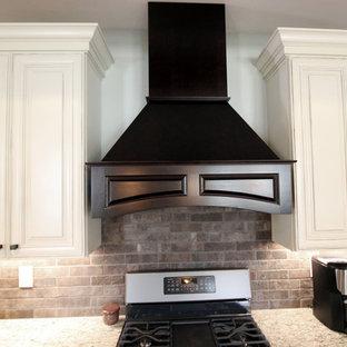 クリーブランドの中サイズのトランジショナルスタイルのおしゃれなキッチン (シングルシンク、フラットパネル扉のキャビネット、ベージュのキャビネット、御影石カウンター、茶色いキッチンパネル、レンガのキッチンパネル、シルバーの調理設備の、無垢フローリング) の写真
