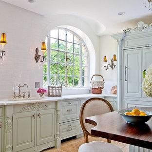 Bild på ett avskilt, mellanstort shabby chic-inspirerat u-kök, med träbänkskiva, gröna skåp, en undermonterad diskho, luckor med upphöjd panel, vitt stänkskydd, stänkskydd i tunnelbanekakel, integrerade vitvaror och klinkergolv i keramik