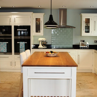 Eat-in kitchen - mid-sized traditional u-shaped travertine floor eat-in kitchen idea in West Midlands with an undermount sink, shaker cabinets, white cabinets, granite countertops, green backsplash, ceramic backsplash, an island and black appliances
