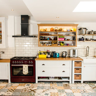 Example of a cottage l-shaped multicolored floor kitchen design in Other with a farmhouse sink, shaker cabinets, white cabinets, wood countertops, beige backsplash, subway tile backsplash, colored appliances and no island