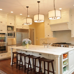 Traditional kitchen ideas - Kitchen - traditional kitchen idea in New York with stainless steel appliances, recessed-panel cabinets, white cabinets, marble countertops, white backsplash and subway tile backsplash