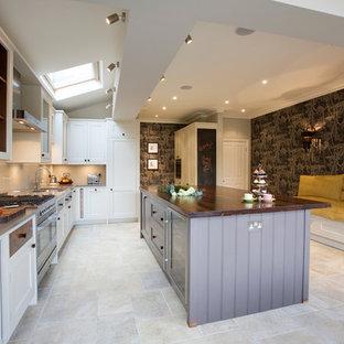 ロンドンの広いヴィクトリアン調のおしゃれなキッチン (アンダーカウンターシンク、落し込みパネル扉のキャビネット、白いキャビネット、木材カウンター、ベージュキッチンパネル、ガラス板のキッチンパネル、シルバーの調理設備、トラバーチンの床) の写真
