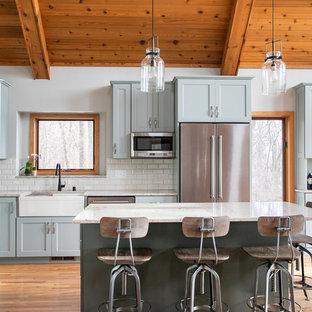 Ejemplo de cocina en L, rural, con fregadero sobremueble, armarios estilo shaker, puertas de armario grises, salpicadero blanco, salpicadero de azulejos tipo metro, electrodomésticos de acero inoxidable, suelo de madera en tonos medios, una isla y encimeras blancas