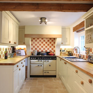 Example of a mountain style enclosed kitchen design in Hampshire with wood countertops, white appliances and a drop-in sink
