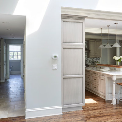 Example of a huge classic l-shaped medium tone wood floor open concept kitchen design in Chicago with a single-bowl sink, recessed-panel cabinets, gray cabinets, quartzite countertops, multicolored backsplash, mosaic tile backsplash, stainless steel appliances and an island