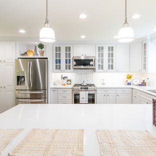 This is an example of a mid-sized traditional u-shaped eat-in kitchen in Orange County with an undermount sink, raised-panel cabinets, white cabinets, quartz benchtops, white splashback, ceramic splashback, stainless steel appliances and porcelain floors.