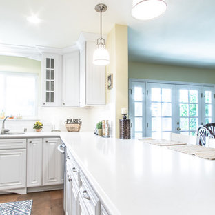 Photo of a mid-sized shabby-chic style u-shaped eat-in kitchen in Orange County with an undermount sink, raised-panel cabinets, white cabinets, quartz benchtops, white splashback, ceramic splashback, stainless steel appliances and porcelain floors.