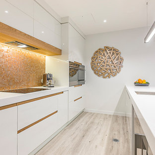 Photo of a mid-sized contemporary galley eat-in kitchen in Auckland with an undermount sink, white cabinets, orange splashback, mosaic tile splashback, stainless steel appliances, flat-panel cabinets, solid surface benchtops, light hardwood floors, a peninsula and multi-coloured floor.
