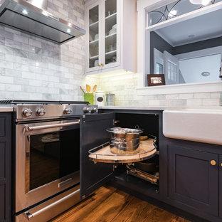 Geschlossene, Kleine Moderne Küche ohne Insel in U-Form mit Landhausspüle, Schrankfronten mit vertiefter Füllung, weißen Schränken, Quarzwerkstein-Arbeitsplatte, Küchenrückwand in Weiß, Rückwand aus Metrofliesen, Küchengeräten aus Edelstahl, braunem Holzboden und braunem Boden in Chicago
