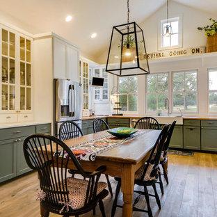 Cette photo montre une cuisine américaine nature en U avec un évier de ferme, un placard à porte vitrée, des portes de placards vertess, un plan de travail en bois, un électroménager en acier inoxydable et un sol en bois clair.