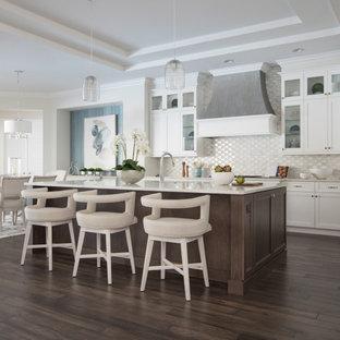 Idéer för ett klassiskt vit parallellkök, med skåp i shakerstil, vita skåp, vitt stänkskydd, mörkt trägolv, en köksö och brunt golv