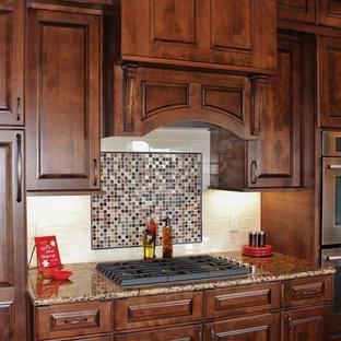 Medium sized traditional u-shaped kitchen/diner in Denver with a submerged sink, raised-panel cabinets, dark wood cabinets, granite worktops, beige splashback, stainless steel appliances, medium hardwood flooring and a breakfast bar.