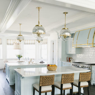 This is an example of a large beach style eat-in kitchen in Los Angeles with a drop-in sink, shaker cabinets, blue cabinets, marble benchtops, white splashback, ceramic splashback, stainless steel appliances, dark hardwood floors, multiple islands, brown floor, white benchtop and coffered.