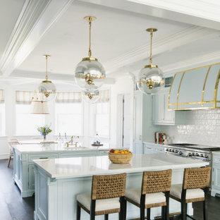 ロサンゼルスの広いビーチスタイルのおしゃれなキッチン (ドロップインシンク、シェーカースタイル扉のキャビネット、青いキャビネット、大理石カウンター、白いキッチンパネル、セラミックタイルのキッチンパネル、シルバーの調理設備、濃色無垢フローリング、茶色い床、白いキッチンカウンター、格子天井) の写真