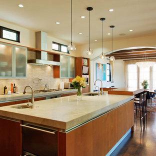 Inspiration för ett medelhavsstil kök, med beige stänkskydd, stänkskydd i stickkakel, en undermonterad diskho, släta luckor, skåp i mellenmörkt trä, rostfria vitvaror, mellanmörkt trägolv och en köksö