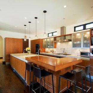 ロサンゼルスの地中海スタイルのおしゃれなキッチン (木材カウンター、アンダーカウンターシンク、フラットパネル扉のキャビネット、中間色木目調キャビネット、ベージュキッチンパネル、ボーダータイルのキッチンパネル、シルバーの調理設備、無垢フローリング) の写真
