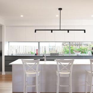 Exemple d'une cuisine bord de mer avec un évier 3 bacs, un placard à porte plane, des portes de placard blanches, une crédence en fenêtre, un électroménager en acier inoxydable, un sol en bois clair, un îlot central, un sol beige et un plan de travail gris.