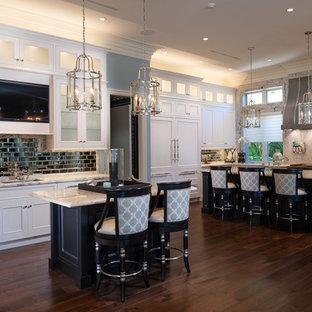 Exempel på ett avskilt, stort klassiskt l-kök, med en undermonterad diskho, luckor med glaspanel, vita skåp, stänkskydd med metallisk yta, stänkskydd i metallkakel, integrerade vitvaror, mörkt trägolv, flera köksöar, marmorbänkskiva och brunt golv