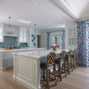 Modelo de cocina lineal, marinera, abierta, con puertas de armario blancas, encimera de mármol, salpicadero azul, salpicadero con mosaicos de azulejos, suelo de madera clara, dos o más islas y armarios con paneles empotrados