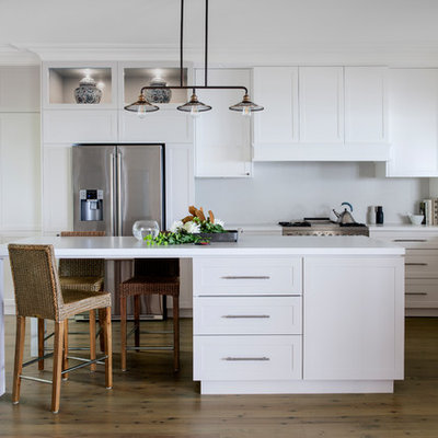 Example of a transitional l-shaped medium tone wood floor and brown floor kitchen design in Sydney with an undermount sink, shaker cabinets, white cabinets, stainless steel appliances, an island and white countertops