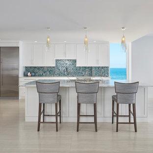 Idées déco pour une grande cuisine ouverte bord de mer en L avec un placard à porte shaker, des portes de placard blanches, un électroménager en acier inoxydable, un îlot central, un évier encastré, un plan de travail en marbre, une crédence bleue, une crédence en carreau de verre, un sol en carrelage de porcelaine, un sol gris et un plan de travail blanc.