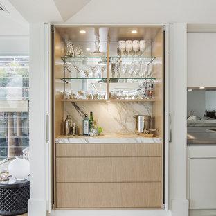 Foto de cocina lineal, minimalista, grande, abierta, con fregadero integrado, armarios con paneles lisos, puertas de armario beige, encimera de mármol, salpicadero metalizado, salpicadero con efecto espejo, electrodomésticos negros, suelo de madera clara y una isla