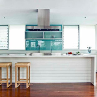 Example of a coastal galley medium tone wood floor kitchen design in Sydney with white cabinets, blue backsplash, glass sheet backsplash and an island