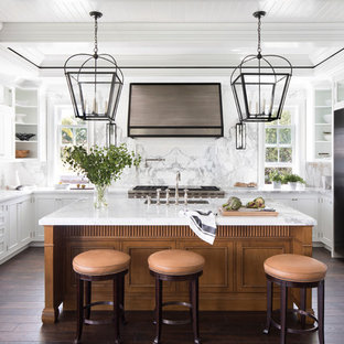 Foto på ett maritimt flerfärgad u-kök, med en undermonterad diskho, luckor med infälld panel, vita skåp, marmorbänkskiva, stänkskydd i marmor, rostfria vitvaror, mörkt trägolv, en köksö, brunt golv och flerfärgad stänkskydd