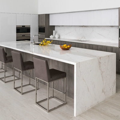Kitchen - contemporary beige floor kitchen idea in Los Angeles with an undermount sink, flat-panel cabinets, white cabinets, white backsplash, stone slab backsplash, paneled appliances, an island and white countertops