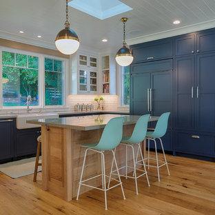 Klassisk inredning av ett mellanstort kök, med en rustik diskho, skåp i shakerstil, blå skåp, bänkskiva i återvunnet glas, vitt stänkskydd, stänkskydd i tunnelbanekakel, integrerade vitvaror, mellanmörkt trägolv och en köksö