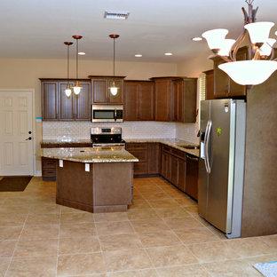 Bild på ett mellanstort tropiskt kök, med en undermonterad diskho, luckor med lamellpanel, skåp i mörkt trä, granitbänkskiva, vitt stänkskydd, stänkskydd i tunnelbanekakel, rostfria vitvaror, klinkergolv i keramik och en köksö