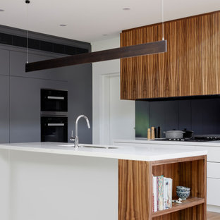 Design ideas for a mid-sized contemporary galley open plan kitchen in Melbourne with an undermount sink, flat-panel cabinets, white cabinets, solid surface benchtops, black splashback, glass sheet splashback, panelled appliances, medium hardwood floors, with island and white benchtop.