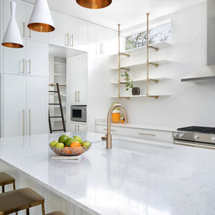 Inspiration for a large midcentury l-shaped eat-in kitchen in Austin with a drop-in sink, flat-panel cabinets, white cabinets, marble benchtops, white splashback, ceramic splashback, stainless steel appliances, concrete floors, with island, grey floor and white benchtop.