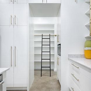 オースティンの広いミッドセンチュリースタイルのおしゃれなキッチン (ドロップインシンク、フラットパネル扉のキャビネット、白いキャビネット、ラミネートカウンター、白いキッチンパネル、シルバーの調理設備、コンクリートの床、茶色い床、グレーのキッチンカウンター) の写真