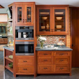 フェニックスの大きいおしゃれなキッチン (ドロップインシンク、落し込みパネル扉のキャビネット、中間色木目調キャビネット、ソープストーンカウンター、マルチカラーのキッチンパネル、モザイクタイルのキッチンパネル、白い調理設備、コンクリートの床、グレーの床) の写真