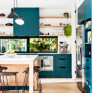 Inspiration for a mid-sized contemporary u-shaped kitchen in Sydney with marble benchtops, white splashback, brick splashback, stainless steel appliances, with island, white benchtop, flat-panel cabinets, turquoise cabinets, light hardwood floors and beige floor.